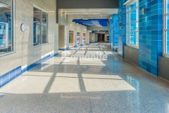 Grain Valley High School enlisted Musselman & Hall Contractors to utilize the Bomanite Modena SL Custom Polishing System to remodel the flooring in their main entrance and hallways and the mixture of blue glass and mirror glass aggregates that was incorporated highlights the grit and shine of the polished concrete.