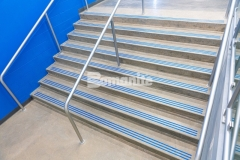 "Bomanite Modena SL was the product of choice to custom polish several sets of concrete steps at Grain Valley High School and the addition of the three-line nose detail engraved into the surface was filled with ""Grain Valley Blue"" epoxy creates to create a unique design element that proudly displays the school's colors."