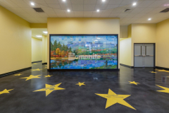 Premier Concrete Construction created custom polished concrete flooring inside the Park Theatre in Jaffrey, NH using Bomanite Custom Polishing Systems with installations of Raven Black integrally colored Bomanite Renaissance for the beautiful, black base flooring and Bomanite Modena TG with three different colors and sizes of yellow glass along with mirror glass to create the stunning star insets.
