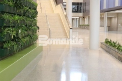 The Bomanite Renaissance Deep Grind System involved treating the floor with chemical hardeners, which minimizes porosity and makes the fully exposed hard aggregates the predominate wear surface, allowing the floor to wear naturally while supporting superior stain resistance and providing a high-end, customizable decorative concrete surface.