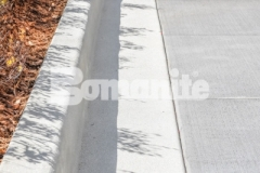 The Bomanite Sandscape Refined Exposed Aggregate System was installed here using a white color hardener in combination with locally sourced aggregates and crushed mirror glass to create a distinctive effect resembling the sun reflecting off water on the curbs and walkways.