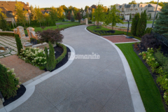 This driveway features Bomanite Sandscape Texture decorative concrete that was installed with Buckskin Integral Color for the main driveway and the banding along the driveway was formed and poured separately using a Limestone textured finish, which resulted in this beautiful and unique design feature that complements the home's exterior and provides durability.
