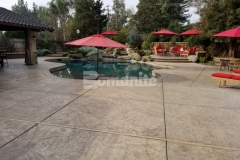 The Bomacron Slate Texture imprint pattern was utilized here with Bomanite Sand Color Hardener and Bomanite Light Brown Release Agent to create an expansive backyard pool deck and patio that beautifully enhance the natural aesthetic in this backyard oasis.
