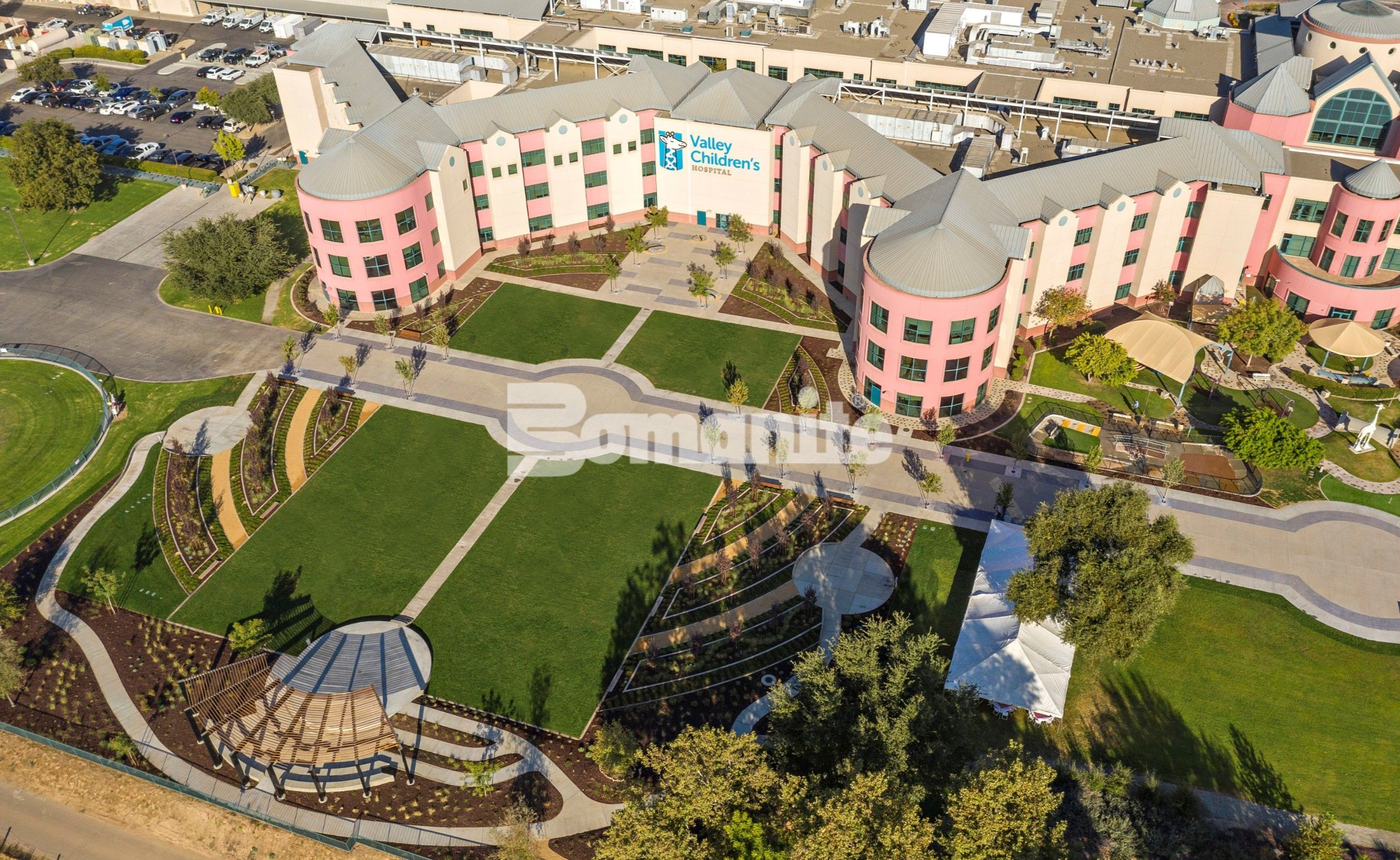 Aerial overhead view of Valley Children's Hospital Grounds where Valley Children's Healthcare Network implements their Landscaping Master Plan Phase 2 with Bomanite Decorative Exposed Aggregate Revealed and Sandscape Texture Systems installed by Heritage Bomanite located in Fresno, CA creating an artistic yet functional design for fundraising events and vehicle traffic.