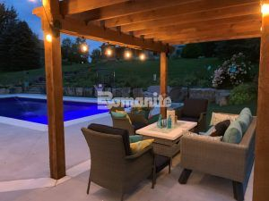 Seating area under pergola including concrete table at one end of the pool at a sparkling updated backyard retreat transformation using Bomanite Revealed Exposed Aggregate System and installed by Concrete Arts, Inc.